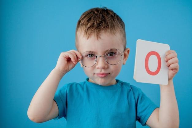 Милый маленький мальчик с письмом на голубой стене. ребенок учится буквы. алфавит