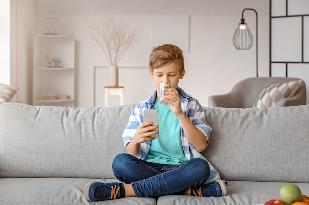 Cute little boy with mobile phone drinking water at home