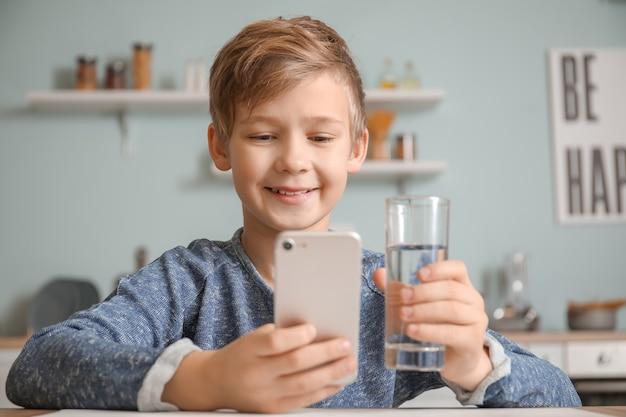 Милый маленький мальчик с питьевой водой мобильного телефона на кухне