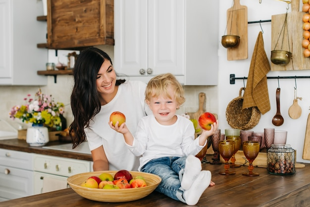 Cute little boy with mother. family in the kitchen: mother with son eating fruit and playing.