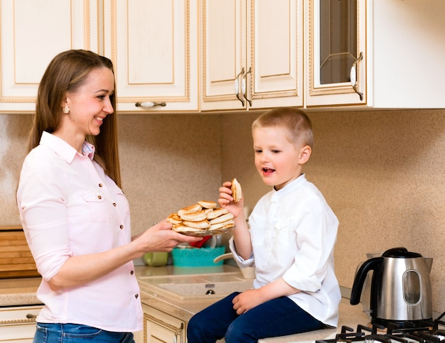 Cute little boy with mother. family in the kitchen. mother with son eating pancakes. homemade baking
