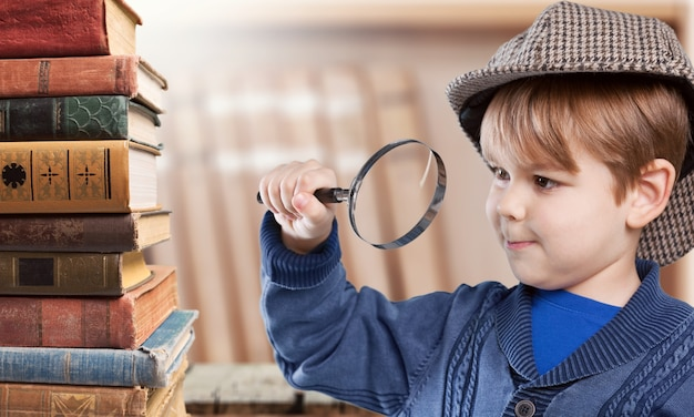 Cute little boy with old books and magnifying glass