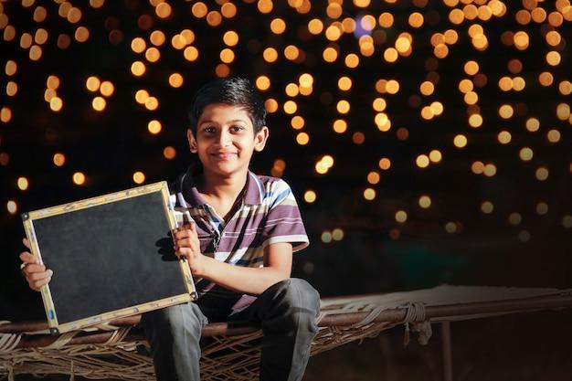Cute little boy with showing slate