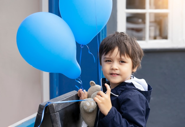 Cute little boy with teddy bear holding blue balloon with smiling face, happy child playing with air balloons outdoor, kid having fun playing outside in spring or summer