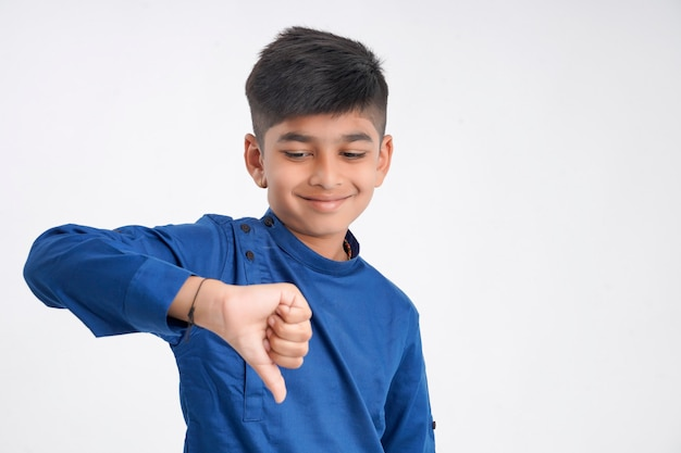 Cute little boy with thump down gesture on white background