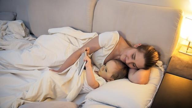 寝る前にタブレットでビデオを見ている若い母親とかわいい男の子。