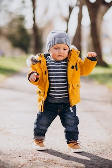 Cute little boy in yellow jacket doing first baby steps