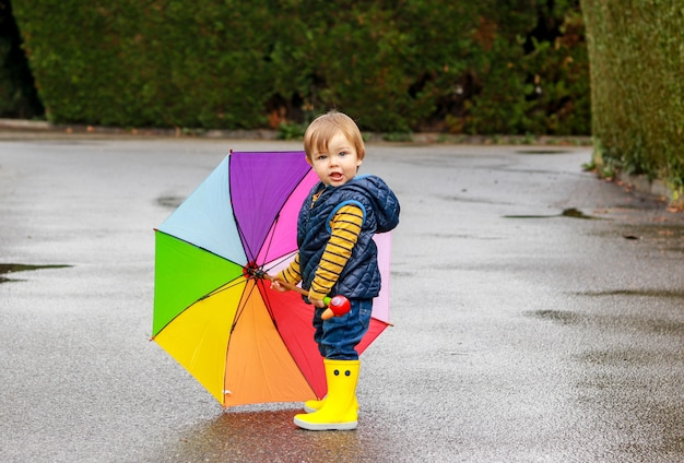 Cute little boy in yellow rubber boots with colorful rainbow umbrella staying on wet road