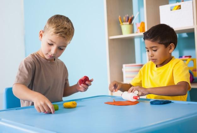 かわいい少年が教室で粘土をモデル化して遊んでいる