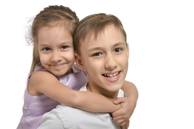 白い背景で抱き締めるかわいい弟と妹
