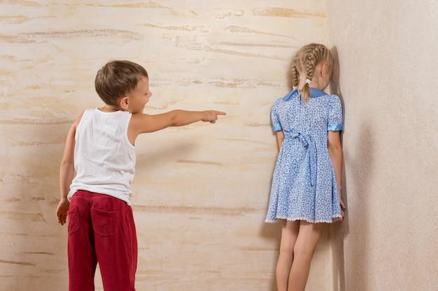 나무 벽에 직면 그의 여동생에게 웃는 귀여운 동생