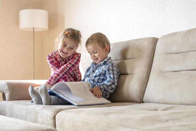 Piccolo fratello e sorella svegli che leggono un libro insieme sul divano a casa