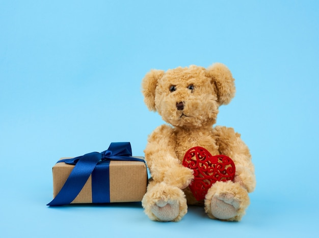 Cute little brown teddy bear holds a brown box with a blue ribbon
