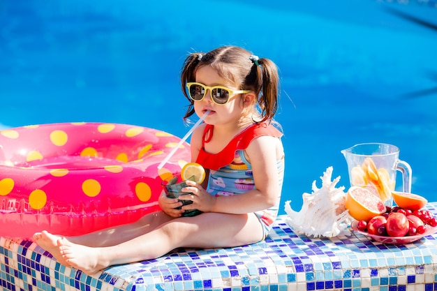 Cute little brunette girl in sunglasses and swimsuit drinks lemonade by the pool.