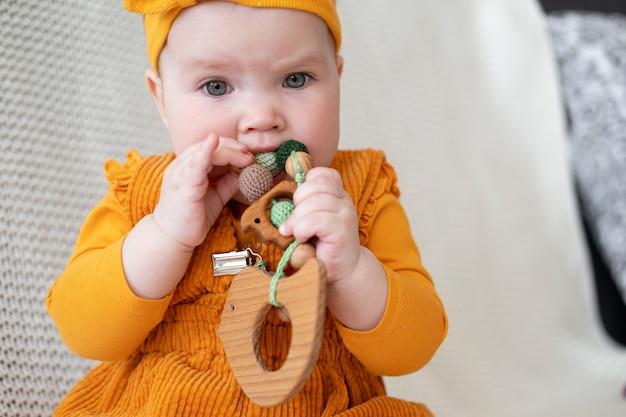 녹색 젖니가 남 구슬을 씹는 귀여운 백인 아기 소녀. 어린 아이들을위한 장난감. 초기 개발