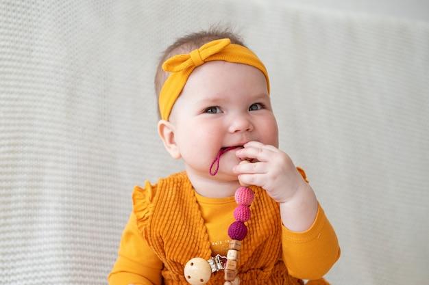 분홍색 젖니가 남 구슬을 씹는 귀여운 작은 있으면 백인 아기 소녀. 어린 아이들을위한 장난감. 초기 개발