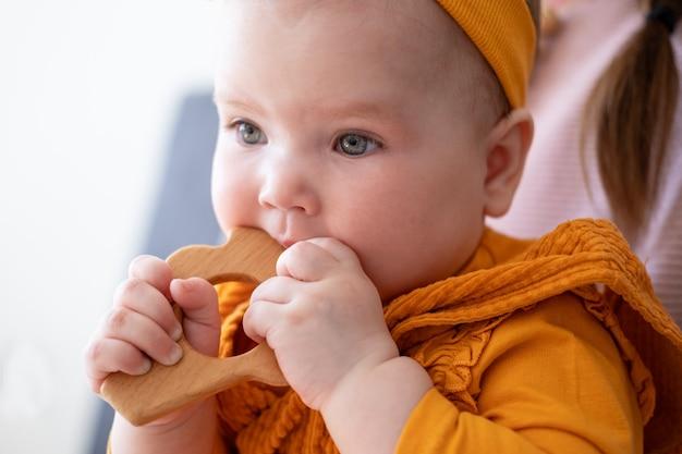 かわいい小さな白人の女の赤ちゃんが木製の歯が生えるビーズを噛んでいます。小さな子供のためのおもちゃ。初期の開発