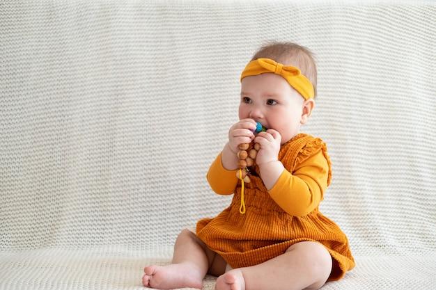 Милая маленькая кавказская девочка играет с жевательными бусинами при прорезывании зубов. мелкая моторика. игрушки для маленьких детей. ранняя разработка