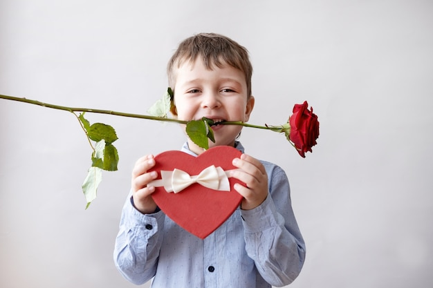 Cute little caucasian boy in bow tie with red heart gift box white ribbon and rose in mouth on light grey background. valentine day.