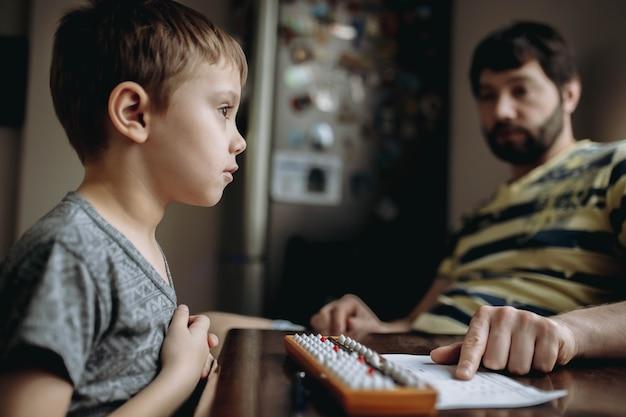 台所のテーブルで彼の隣に座っている父親と暗算の宿題をしているかわいい白人の男の子。高品質の写真