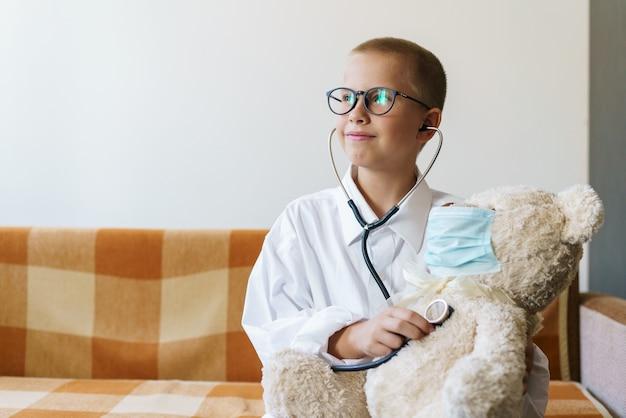귀여운 백인 소년이 장난감을 듣고 청진기를 들고 의사처럼 재미있는 게임을 하고 있습니다.
