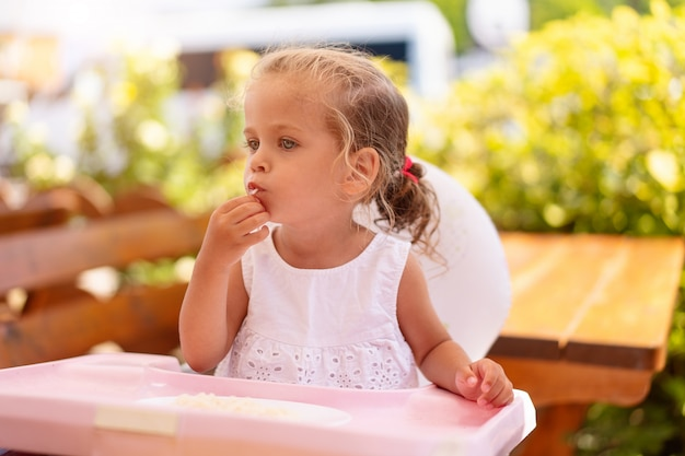 Милая маленькая кавказская девушка есть спагетти на таблице сидя в ресторане детского сиденья внешнем. здоровое питание. смешной ребенок ест уличной еды солнечный летний день.