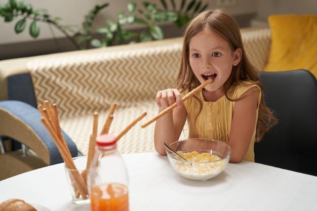 집에서 아침을 먹고 우유와 간식으로 시리얼을 먹고 웃고 있는 귀여운 백인 소녀