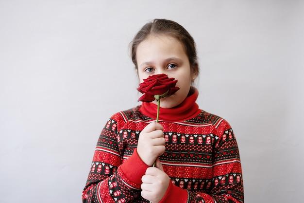 장미와 빨간 드레스에 귀여운 작은 백인 여자. 발렌타인 데이.