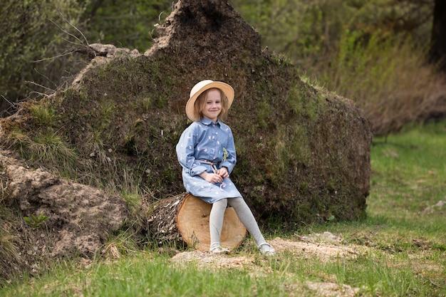 かわいい白人の女の子が森の鋸で挽かれた丸太の上に座って、その隣に上向きの根を持つ倒れた木があります