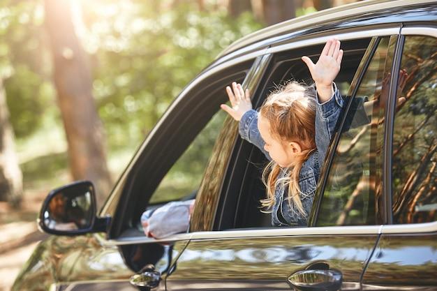 車の中に座って、窓の家族の道の外を見ているかわいい白人の女の子