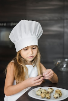 Cute little chef peeing quail eggs shell in kitchen
