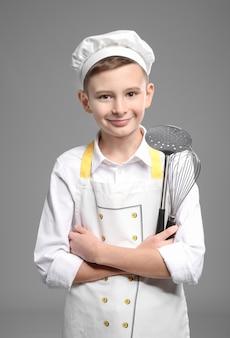 Милый маленький повар с кухонной утварью на сером фоне
