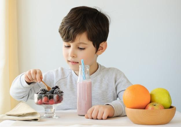 ベリー、屋内でヨーグルト、子供の食べ物、子供のための健康食品を食べるかわいい小さな子供の男の子