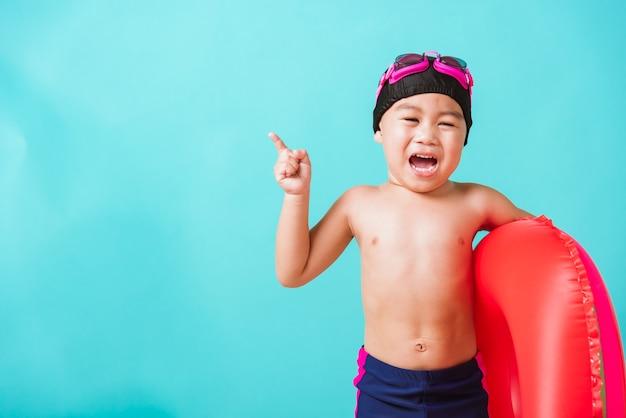 Милый маленький ребенок мальчик в очках и купальнике держит надувное кольцо с арбузом