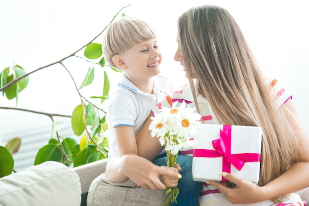 Cute little child congratulates his mother with mothers day