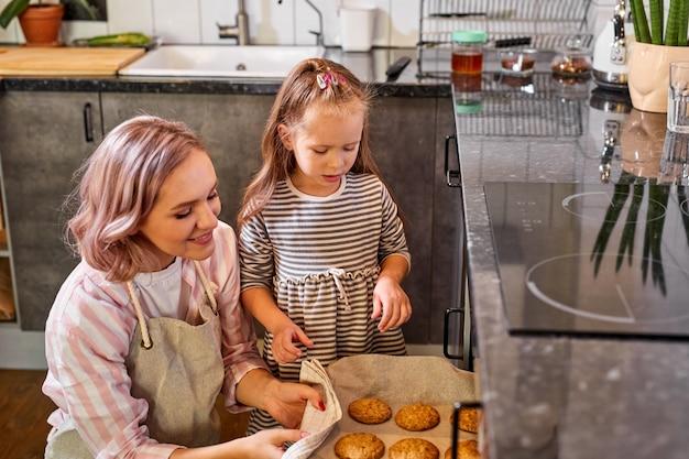 かわいい小さな子供の娘は、お母さんがキッチンオーブンでクッキーを焼くのを手伝って、彼らはそれの準備ができているのを見て立っています