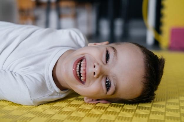 マットな子供の脳性麻痺のかわいい小さな子供障害者の少年