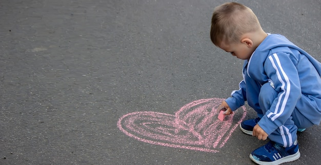 Милый маленький ребенок рисует мелом на открытом воздухе