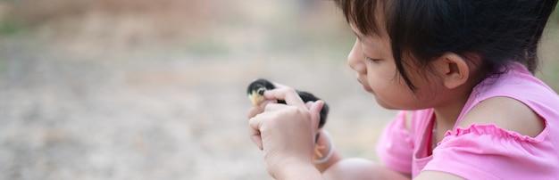 사랑과 행복으로 아기 병아리를 손에 들고 있는 귀여운 어린 소녀