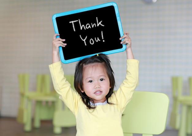 Cute little child girl holding blackboard showing text