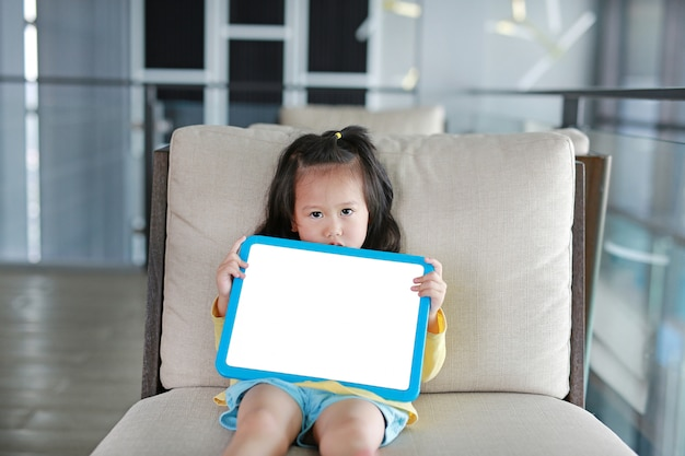Cute little child girl holding empty white blackboard on fabric sofa in library room.