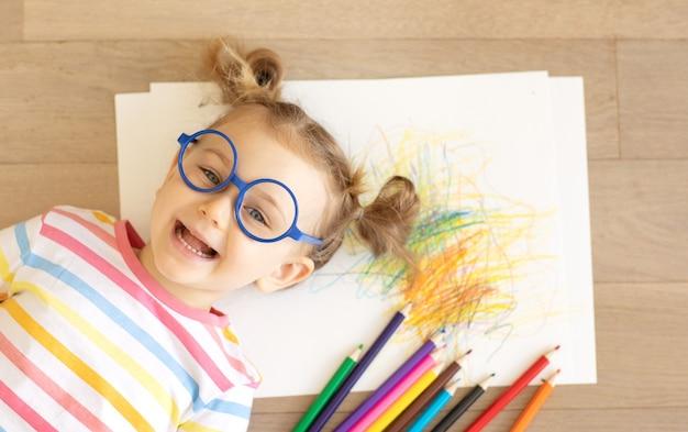 Милая маленькая девочка в очках, лежа на полу, смеясь, эмоциональный ребенок удобно лежит на деревянном полу с бумагой и цветными карандашами. копирование пространства, макет
