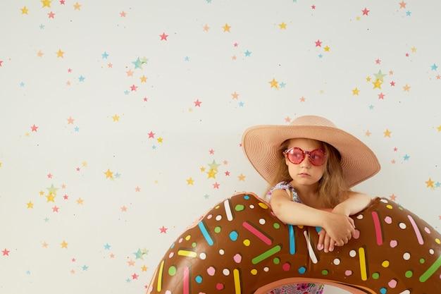 Милая девушка маленького ребенка в шляпе с раздувным кольцом на стене цвета. карантинный летний отдых на дому