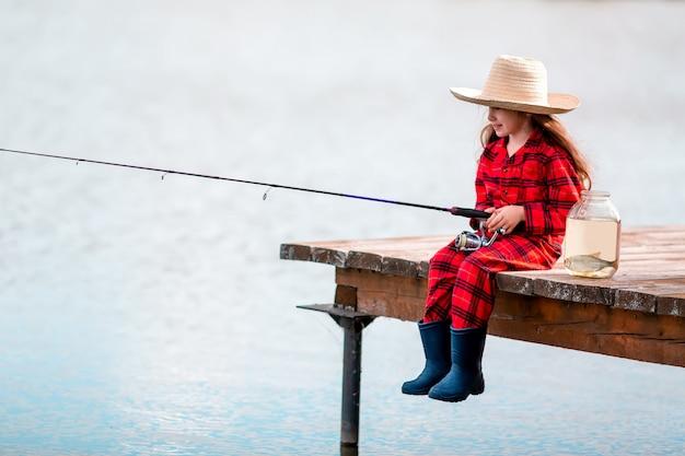 ゴム長靴とガラスの瓶と湖の小さな魚の近くの木製の桟橋から麦わら帽子釣りでかわいい子女の子