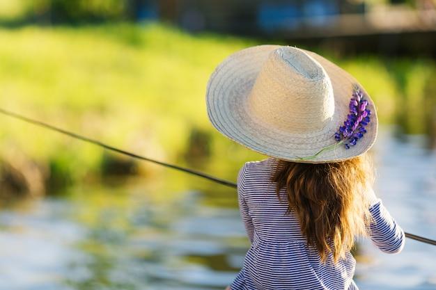Милая девушка маленького ребенка в соломенной шляпе с рыбной ловлей цветка люпина на озере.