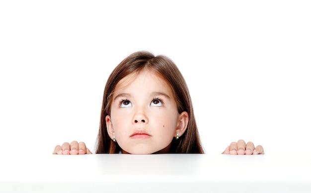 Милая маленькая девочка ребенка, глядя на стол в школе.