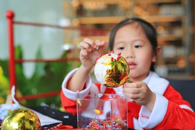 Милая маленькая девочка ребенка, делая рождественский бал украшение украшения