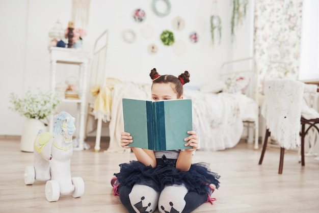 Cute little child girl reading a book in the bedroom. kid with crown sitting on the bed near window