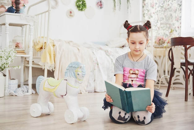 Cute little child girl reading a book in the bedroom.