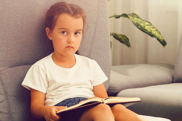 Cute little child girl reading a book